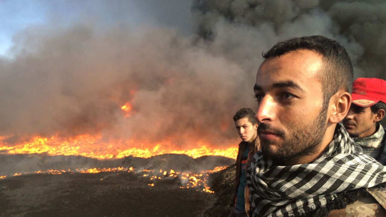 Men standing against a horizon of burning oil fields.